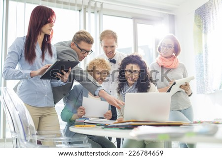 Smiling creative businesspeople working on laptop at desk in office - stock photo