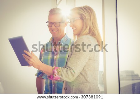 Smiling creative design team using tablet in the office - stock photo