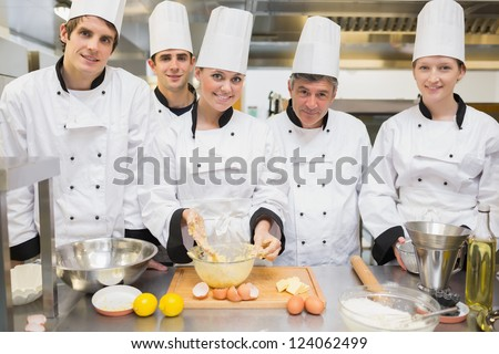 Smiling culinary class with pastry teacher in kitchen - stock photo