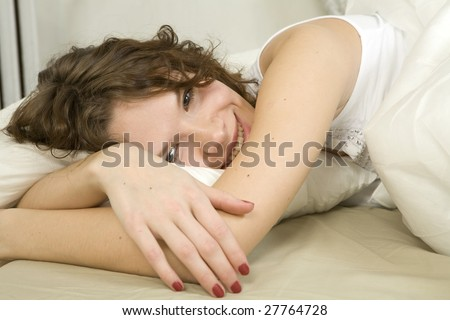 smiling curl adorable woman lying on bed