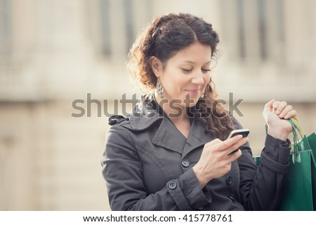 smiling curly woman shop with phone in cityscape
