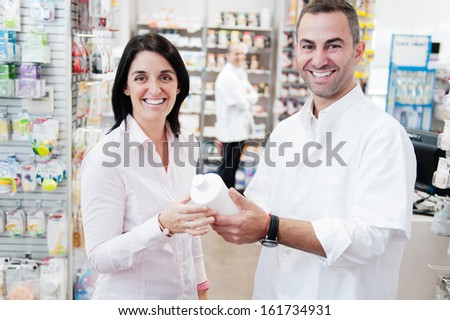 Smiling customer an pharmacist in a pharmacy. In the background we can see another pharmacist - stock photo