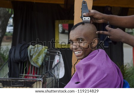Smiling customer at energy efficient African small business barber with inverter and car batteries in trolley