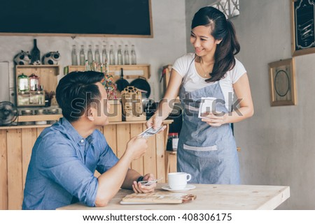 Smiling customer paying by cash at the coffee shop - stock photo