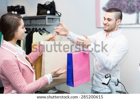 Smiling customer paying for new apparel at store counter - stock photo