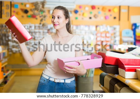 Smiling customer selects  paper boxes  for gifts in the supermarket