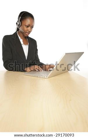 Smiling customer service operator.Female black girl with the headphones - stock photo