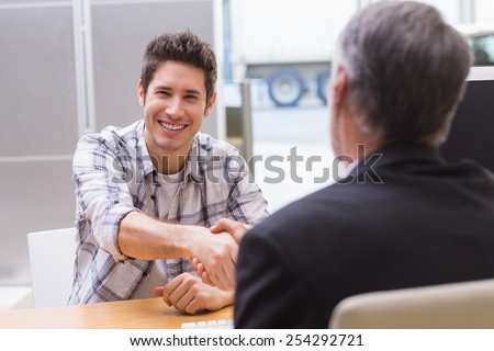 Smiling customer shaking a salesman hand at new car showroom - stock photo
