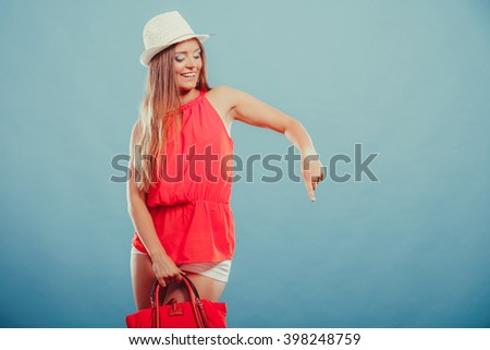 Smiling cute attractive young woman girl in red shirt and hat with handbag and sunglasses in studio on blue showing blank empty copyspace. Summer female fashion  and advertisement. - stock photo
