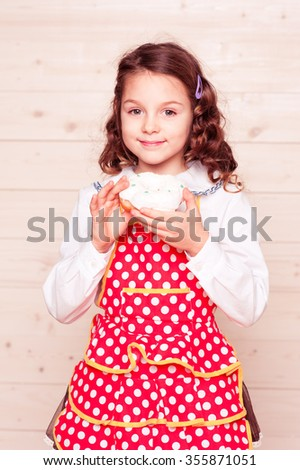 Smiling cute baby girl 5-6 year old eating glazed donut in room. Looking at camera. Childhood.  - stock photo