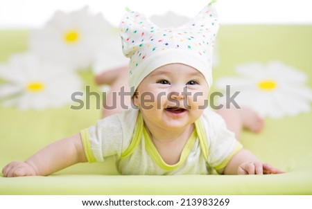 smiling cute baby lying on green - stock photo