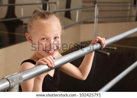 Smiling cute ballet student holds railing in dance studio - stock photo