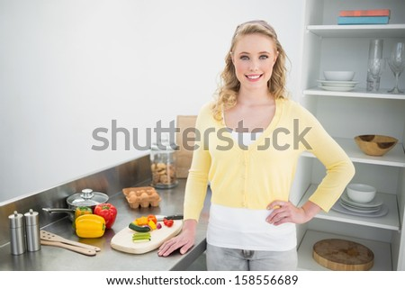 Smiling cute blonde standing hand on hips in bright kitchen