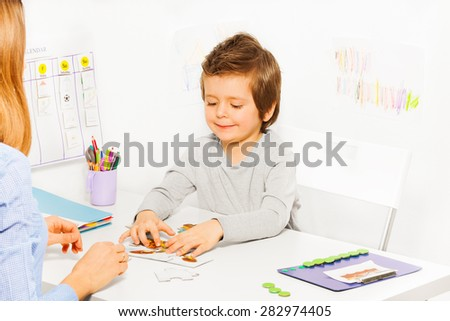 Smiling cute boy plays developing game with parent - stock photo