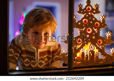 Smiling cute boy standing by window at Christmas time. With colorful lights from Christmas tree on background, selective focus. - stock photo