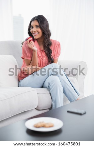 Smiling cute brunette sitting on couch holding red apple in bright living room