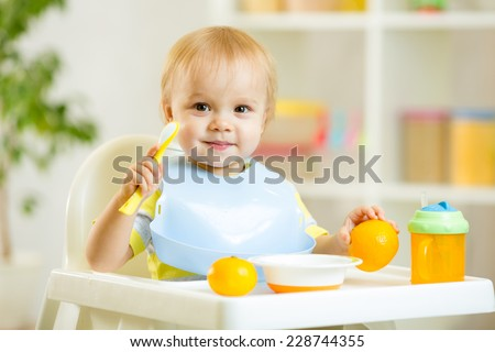 smiling cute child baby boy eating itself with spoon - stock photo