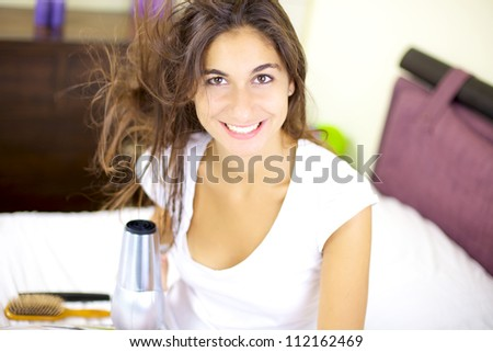 Smiling cute girl dry her hair at home in bed