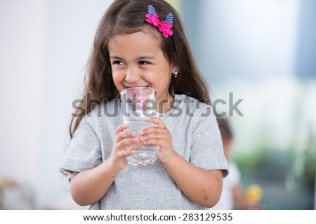 Smiling cute girl holding glass of water at home - stock photo