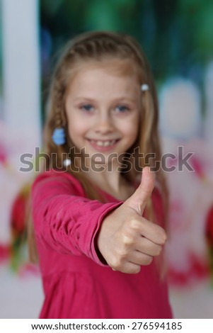 Smiling cute girl shows thumbs up - all will be good - positive lifestyle concept - focus on hand with shallow DOF - stock photo