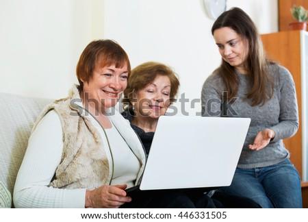 Smiling cute girl teaching positive senior women using laptop in domestic interior - stock photo