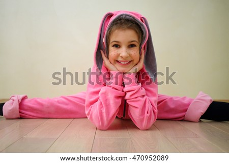Smiling cute girl with flecks of sunlight in bunny suit on floor