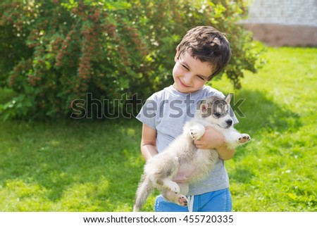 Smiling cute little boy holds on a hands a husky puppy in a garden - stock photo
