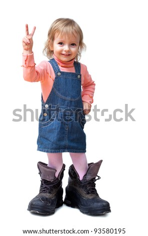 Smiling cute little girl in old big tracking shoes shows V-sign isolated on white - stock photo