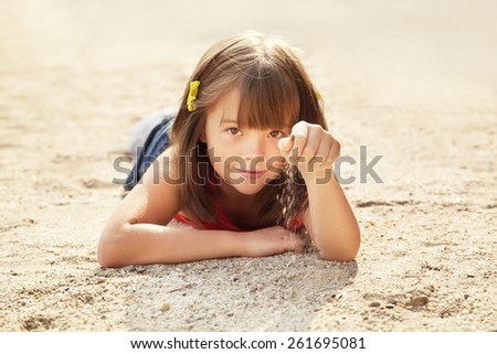 smiling cute little girl lying on the sand. child on vacation outdoor. sea beach - stock photo