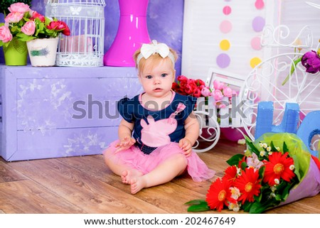 Smiling cute little girl sitting on a house floor among flowers  - stock photo