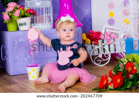 Smiling cute little girl sitting on a house floor among flowers playing - stock photo