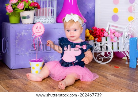 Smiling cute little girl sitting on a house floor among flowers playing  fun - stock photo