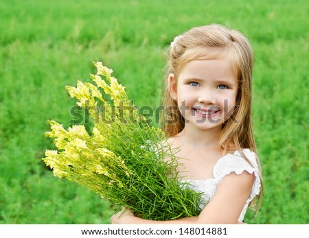 Smiling cute little girl with flowers on the meadow in summer day