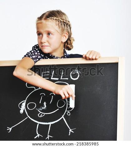 Smiling cute school girl drawing on blackboard - stock photo