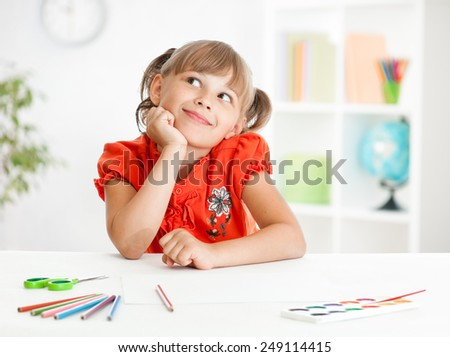 Smiling cute schoolgirl dreaming making homework. Creation concept - stock photo