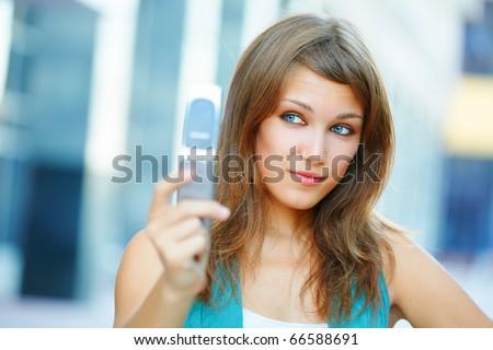 Smiling cute student teenage girl looking at mobile phone. Urban scene, closeup. - stock photo