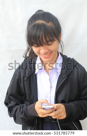 Smiling cute student teenager in Asia is holding on phone standing on white background.