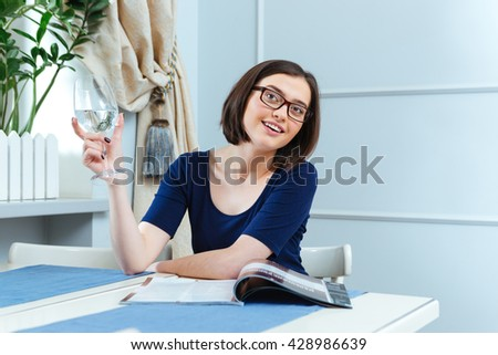 Smiling cute young woman drinking water and waiting for waitress in cafe - stock photo