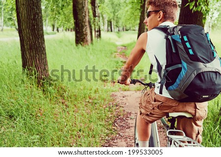 Smiling cyclist man is riding mountain bike on trail in summer park - stock photo