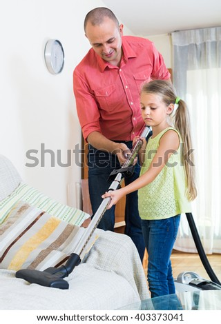 Smiling dad and his little daughter hoovering at home together. Focus on girl