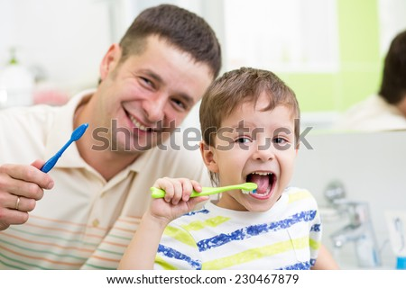 smiling dad and kid son brushing teeth in bathroom - stock photo