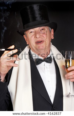 Smiling dandy with a glass of champaign, a monocle and a cigarette holder - stock photo
