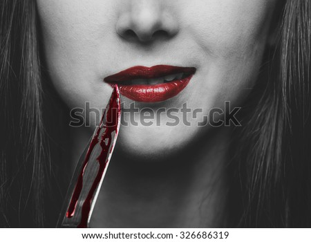 Smiling dangerous young woman with knife in blood. Halloween or horror theme. Black and white image with red elements - stock photo
