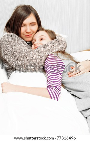 Smiling daughter with her mother laying together at their apartment on bed