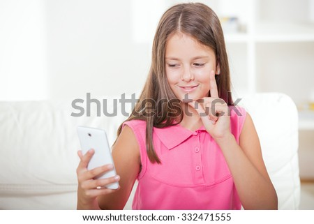 Smiling deaf girl talking using sign language on the smartphone's cam - stock photo