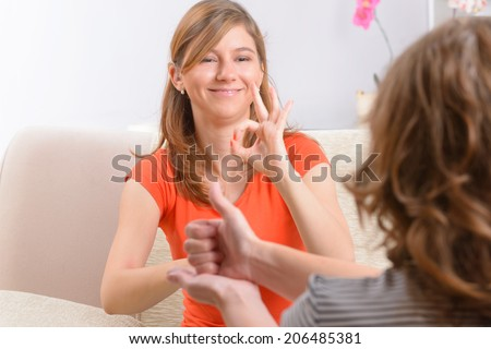 Smiling deaf woman learning sign language - stock photo