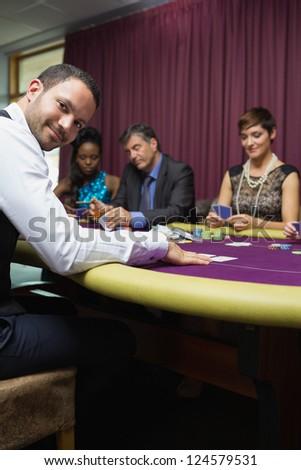 Smiling dealer at poker game in casino - stock photo
