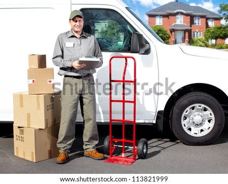 Smiling delivery courier standing near the white truck. Shipping service. - stock photo