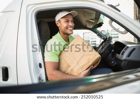 Smiling delivery driver in his van holding parcel outside warehouse - stock photo