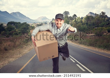 smiling delivery man and road background - stock photo
